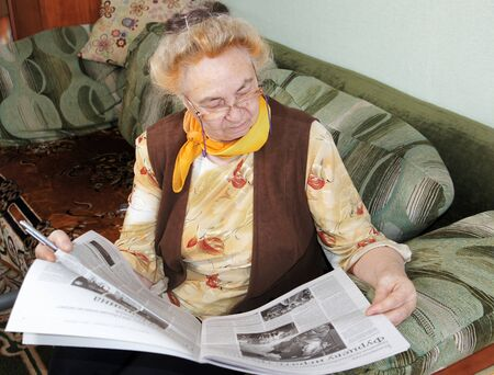 Elderly woman is reading a newspaper photo