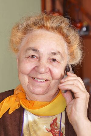 Elderly woman is talking by a mobile phone photo