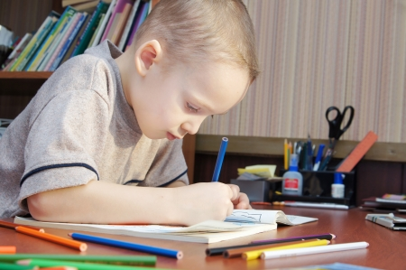 eager: Little boy is drawing with colorful pencils in a book