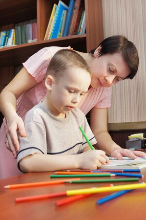 eager: Woman is teaching a little boy to draw Stock Photo