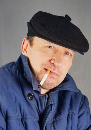 Marginal man in a cap with a cigarette Stock Photo - 17447202