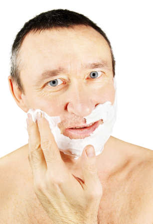 anoint: Man spreads shaving foam on his cheeks Stock Photo