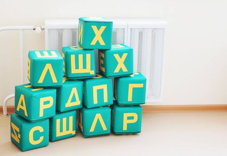 Large cubes with letters of Russian alphabet in a kindergarten