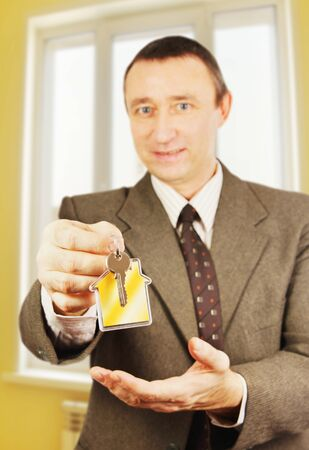 Man gives keys with keychain in the form of a little house into a new apartment Stock Photo - 17641511