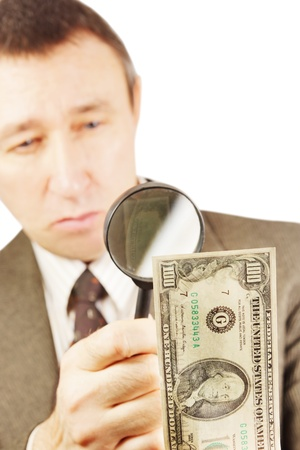 Man looks through a magnifying glass on the dollar banknote