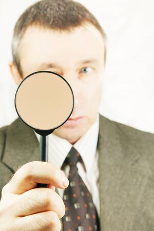 Man looks through a magnifying glass photo