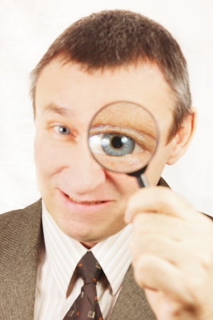 Angry man looks through a magnifying glass photo