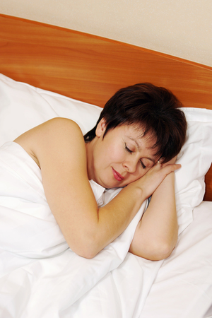 Portrait of a happy beautiful woman sleeping in the bed photo