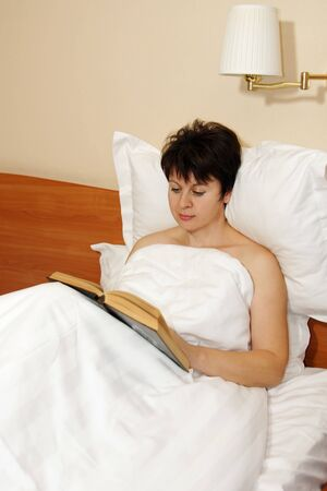 Woman reading a book in the bed before sleeping Stock Photo - 23448557