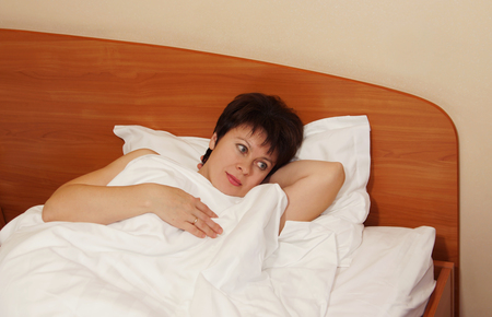 Just awoke woman lies in the bed with open eyes Stock Photo - 23448602