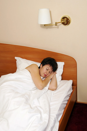 Pretty middle aged woman sleeps in the bed photo