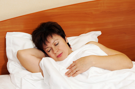 Pretty middle aged woman soundly sleeps in the bed photo