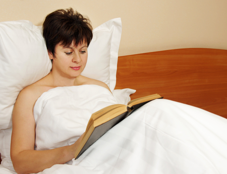 Woman reads a book in the bed before sleeping Stock Photo - 23448603