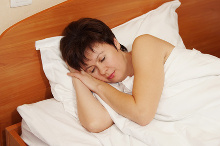 Woman soundly sleeping on a bed photo