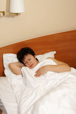 Woman soundly sleeps on a bed photo