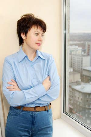 awaiting: Awaiting woman wears a blue shirt stands next to the window Stock Photo
