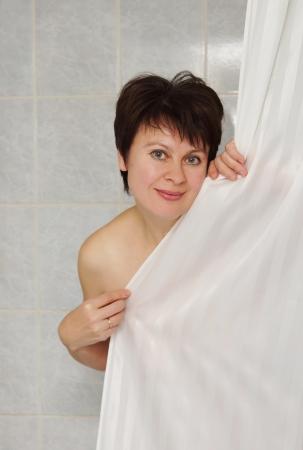 Woman in a bath behind the curtain photo