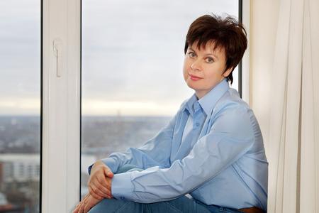 Woman sitting near the window photo