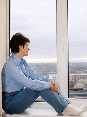 Woman sitting on a windowsill and awaiting photo
