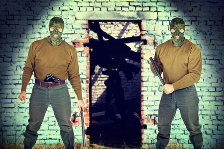 plunder: Two gunmen near the brick wall Stock Photo