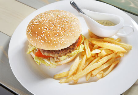 Hamburger with french fries and sauce photo
