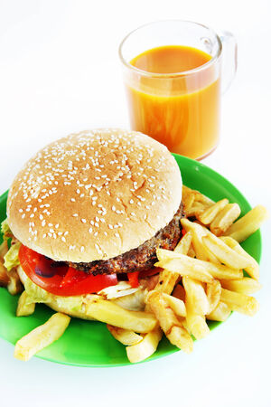 Hamburger with French fries in the plate and a glass of juice photo