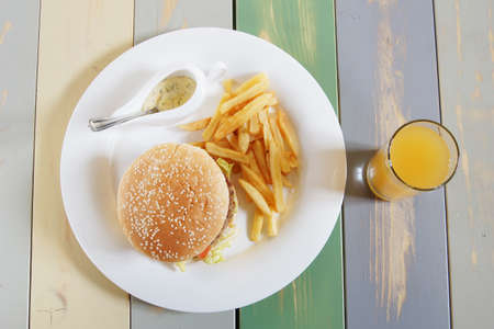 Hamburger with french fries and sauce on the wooden table photo
