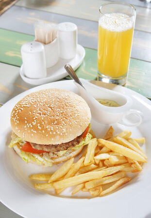 Hamburger with french fries and sauce on the table in cafe photo