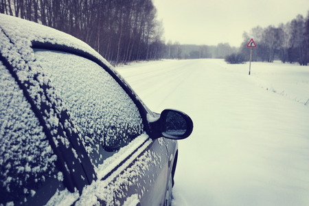 inclement weather: Car on a snowy road (focus on the mirror)