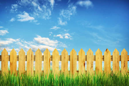 Vivid summer landscape with wooden fence and green grass photo