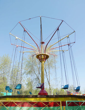Old carousel with seats on chains photo