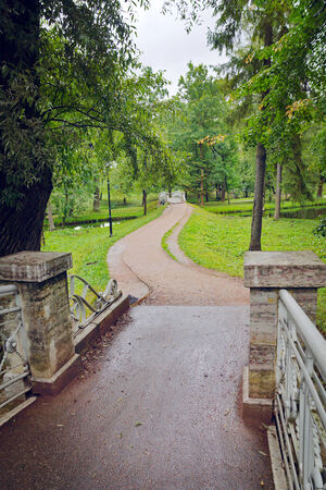 Old bridge with metal railings and a path in the palace park in Gatchina, town near Saint Petersburg, Russia photo
