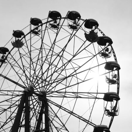 Black and white toned image with an old ferris wheel against the sky