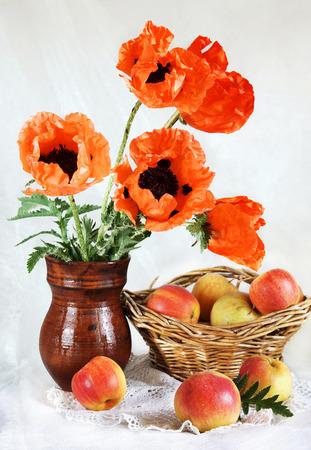 oriental poppy: Still life with red oriental poppy flowers and fresh apples in a wicker basket
