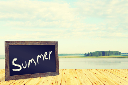 Summer concept with blackboard and calm landscape photo