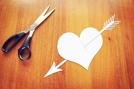 Paper heart pierced by an arrow on the table photo