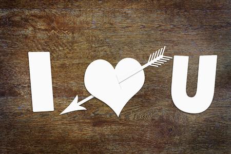 declaration of love: Paper heart pierced by an arrow on wooden background