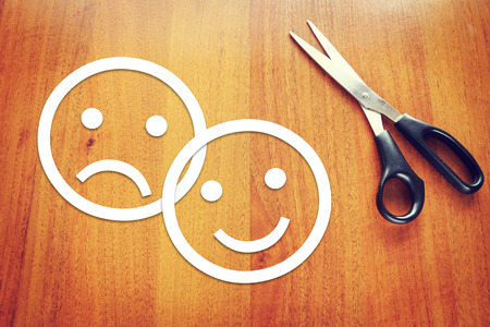 Sad and happy emoticons made of paper on the desk. Concept of various emotions photo