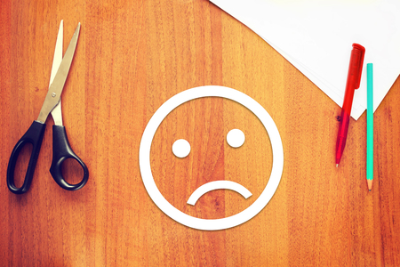 smiley: Sad emoticon made of paper on the desk. Concept of melancholy emotions