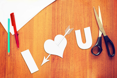 Symbol of love a paper heart pierced by an arrow on the desk photo