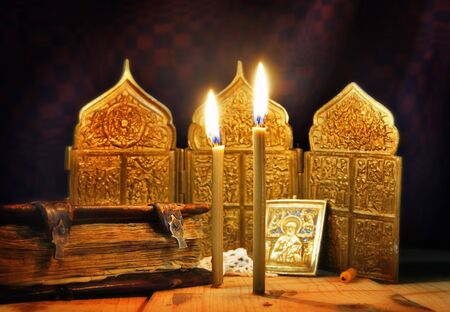 godly: Christian still life with ancient icons and burning candles. Focus on candles Stock Photo