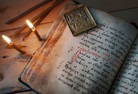 godly: Christian still life with burning candles and old metal icon on the open ancient book Stock Photo