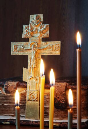 godly: Orthodox Christian still life with metal cross and burning candles Stock Photo