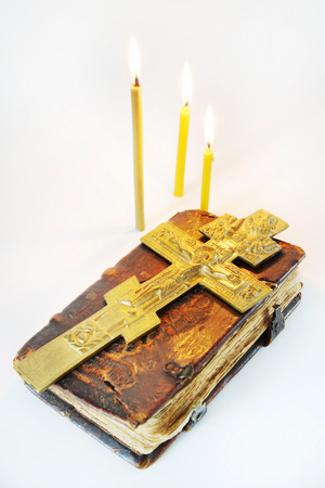 easter candle is burning: Orthodox Christian still life with a metal crucifixion over ancient book on light background