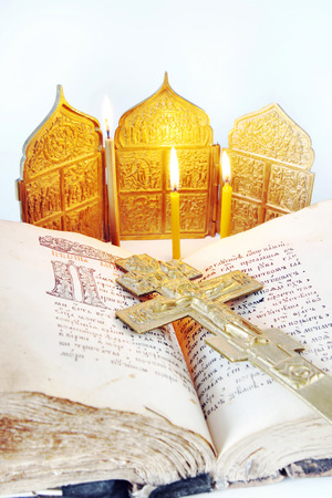 easter candle is burning: Orthodox Christian still life with an open ancient Bible and metal cross on light background Stock Photo
