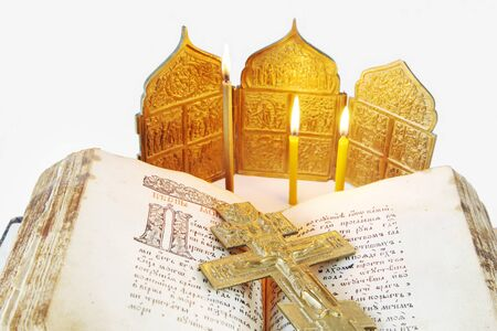 godly: Orthodox Christian still life with an open ancient Bible and metal crucifixion on light background