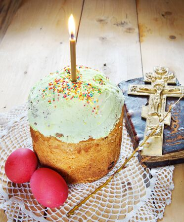 easter candle is burning: Classical Orthodox Christian Easter still life with red eggs and burning candle over the cake Stock Photo
