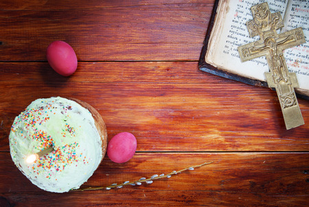 easter candle is burning: Composition about Christian Easter with red eggs and burning candle over the cake