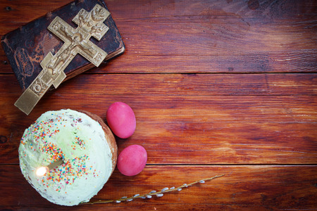 easter candle is burning: Composition about Orthodox Christian Easter with red eggs and burning candle over the cake Stock Photo