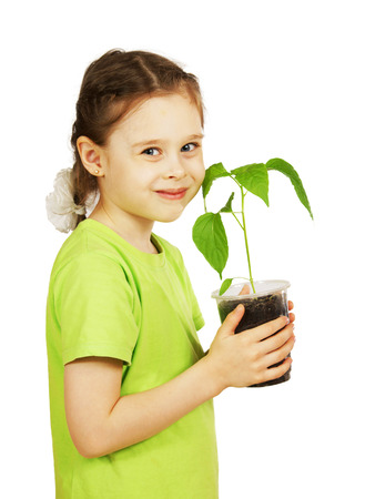 Little girl with a seedling in the pot isolated over white background